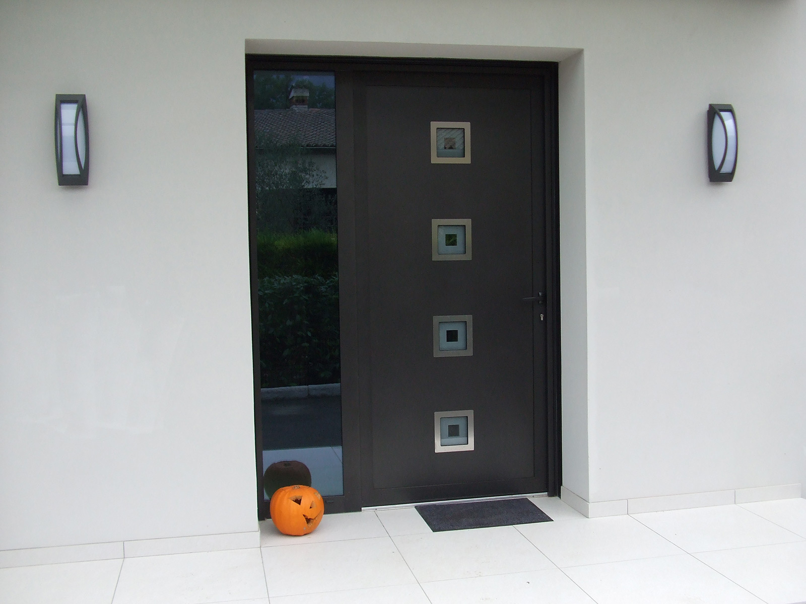 """Photo d""""une réalisation d'une porte d'entrée moderne avec fixe latéral et insert inox"""