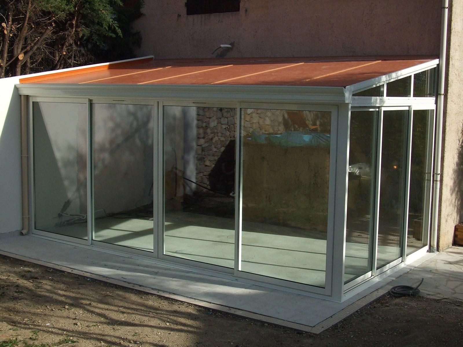 Photo d'une réalisation d'une véranda avec toiture panneaux phonique couleur tuiles